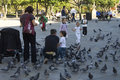 Parents with young children have fun with pigeons spain on the square plaza de la herreria in the spanish city pontevedra people Stock Image