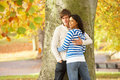 Pares adolescentes románticos por el parque del otoño de Tree In Fotos de archivo libres de regalías