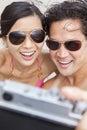 Pares asiáticos na praia que toma a fotografia de selfie Fotos de Stock