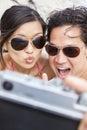Pares asiáticos na praia que toma a fotografia de selfie Fotos de Stock Royalty Free