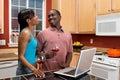 Pares do americano africano usando o portátil na cozinha Imagem de Stock