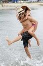 Pares jovenes que juegan en la playa Foto de archivo libre de regalías