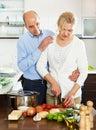 Pares maduros cariñosos que cocinan junto Imagen de archivo