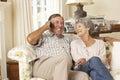 Pares mayores jubilados que se sientan en el hogar de sofa talking on phone at junto Fotos de archivo libres de regalías