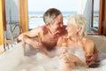 Pares mayores que se relajan en el baño que bebe a champagne together Fotos de archivo libres de regalías