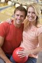 Pares na esfera e no sorriso da terra arrendada da aléia de bowling Imagens de Stock Royalty Free