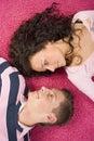 Pares novos que encontram-se no tapete cor-de-rosa Fotografia de Stock