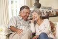 Pares superiores aposentados que sentam se na casa de sofa talking on phone at junto Fotografia de Stock