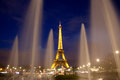 Paris eiffel tower by night with lights on seen from between fountains Royalty Free Stock Photos