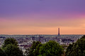 Paris, France - June 1, 2015: Spectacular overview over city with Eiffel tower silhouette against beautiful orange Royalty Free Stock Photo
