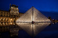 Paris louvre museum in by night with illuminated pyramid and blue sky Stock Photo