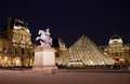 Paris louvre night scene museum in by with illuminated pyramid Stock Photo