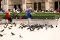 PARIS - May 7: Notre Dame Cathedral on May, 2009 in Paris. Unknown man with pigeons in front of the cathedral was essentially com Royalty Free Stock Photo