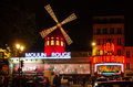 Paris the moulin rouge by night in france is a famous cabaret built in locating in red light district of Stock Photo