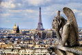 Paris view famous notre dame gargoyle overlooking the cityscape with eiffel tower Royalty Free Stock Images