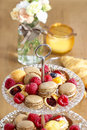 Parisian macarons raspberries and other delicacy closeup festive party dessert Royalty Free Stock Photography
