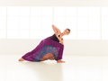 Parivritta parshvakonasana young girl in twisted yoga posture dressed with pants skirt colorful indor Stock Photography