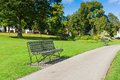 Park alley scene with and old bench Stock Image