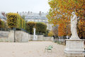 Park in autumn in paris france the statue benches yellow leaves Stock Image