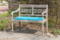 Park bench with blue seat cushions in the garden Royalty Free Stock Photo