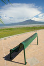 Park bench and mountain green on tiled walkway overlooking lake chapala with clouds blue sky Royalty Free Stock Photography