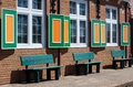 Park benches and pattens green create an interesting pattern under green orange shutters on a brick street Stock Photos
