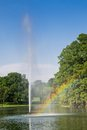 Park fountain with rainbow big in in the right side sunny day clear sky and green vegetation Stock Photos