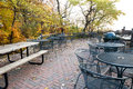 Park patio a brick littered with leaves and surrounded by trees in the fall Stock Photo
