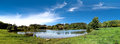 Park scenery a beautiful wide view of a with a pond under a bright cloudy sky Royalty Free Stock Image