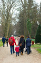 Park walk group of parents walking with their children on a footpath at the arboterum Royalty Free Stock Images