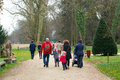 Park walk group of parents walking with their children on a footpath at the arboterum Stock Images