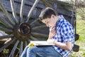 Park young mens die een boek in openlucht met gele appel lezen Royalty-vrije Stock Foto's