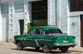 Parked green classic car before a building in the countryside from cuba Royalty Free Stock Photo