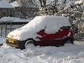 Parked red car under a layer of snow Stock Images