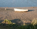 A parked row boat vessel on the beach with footprints too and fr Royalty Free Stock Photo
