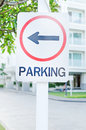 Parking lot sign with left arrow and building in background Royalty Free Stock Photo