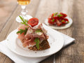 Parma ham sandwich with tomato on a white plate wooden table shallow focus vibrant color Royalty Free Stock Image