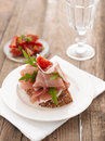 Parma ham sandwich with tomato on a white plate wooden table shallow focus vibrant color Royalty Free Stock Photos
