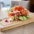 Parma ham sandwich on wooden plate Royaltyfria Bilder
