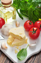 Parmesan cheese with tomatoes and basil in the background Stock Photo