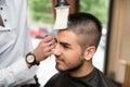 Parrucchiere cleaning young man dopo taglio di capelli Immagini Stock Libere da Diritti