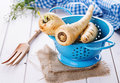 Parsnip in a blue colander over white wooden background group of parsnips on Royalty Free Stock Image