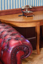 Part of armchair and vintage phone on wooden table red leather Stock Photography
