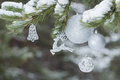 Part of decorated Christmas tree with animal Santa Claus's reindeer ornament and silver baubles on snowy branches Royalty Free Stock Photo