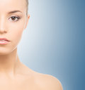Part of a face of a young woman on blue close up spa portrait beautiful and healthy girl over background Stock Photos