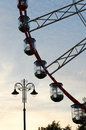 Part of ferris wheel with cabins and lamppost at sunset sky background. Royalty Free Stock Photo