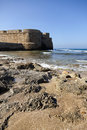 Part of the fortified wall surrounding the ancient city of acco israel bordering with the rocky shore of the mediterranean sea on Stock Photography
