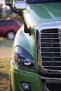 Part of modern semi truck with grille and headlight chrome fog lamp hood fixed mirrors stylish powerful luxury comfortable green Stock Photo