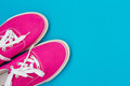Part of the Pink sneakers with white laces on a blue Royalty Free Stock Photo