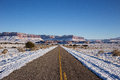 Partially snow covered road in winter view of a leading towards a red rock mountain Royalty Free Stock Photos